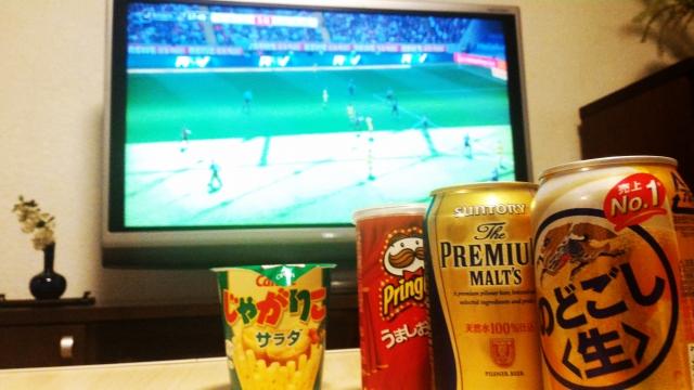 リビングでサッカーが移るテレビと缶ビール2本、お菓子が移った画像