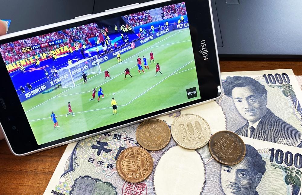 ユーロのサッカーが映るスマートフォンと2,530円の現金