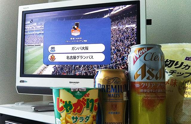 DAZNのJリーグ中継が映ったテレビと、その前に置かれたビールとお菓子